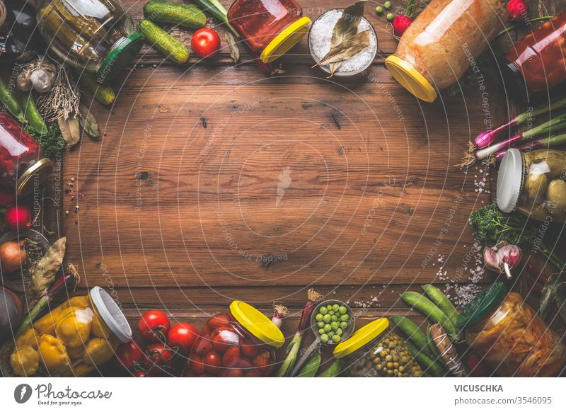 Wooden food background with various preserved vegetables in jars. Homemade harvest canning. Fermented vegetables. wooden fresh ingredients top view frame border