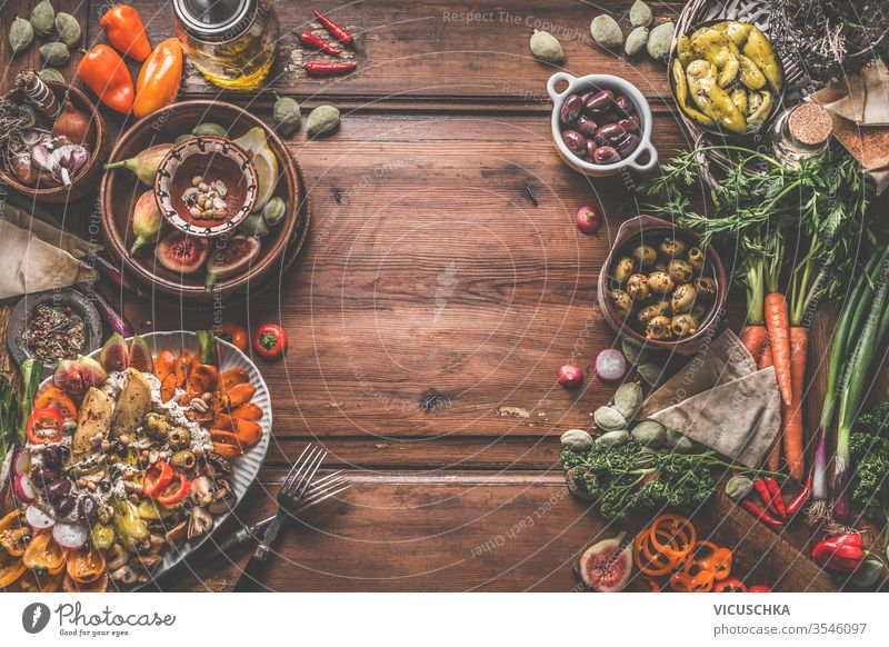 Healthy vegan or vegetarian food background with snacks. Various fresh, pickled and fermented vegetables in bowls. Hummus plate with roasted vegetables and nuts. Olives, figs, green almond , chickpeas