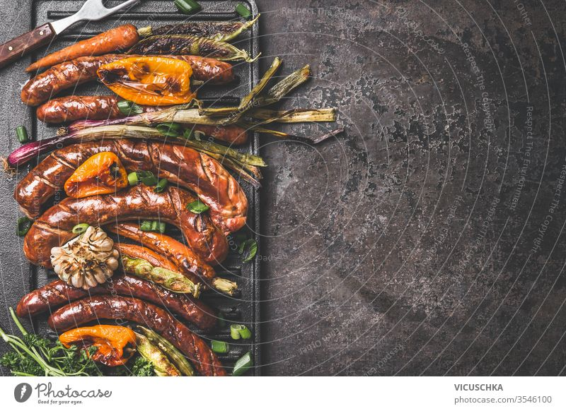 Dark roast food background with grilled sausages and roasted vegetables. Top view. Barbecue grill party plate. dark top view barbecue copy space design product