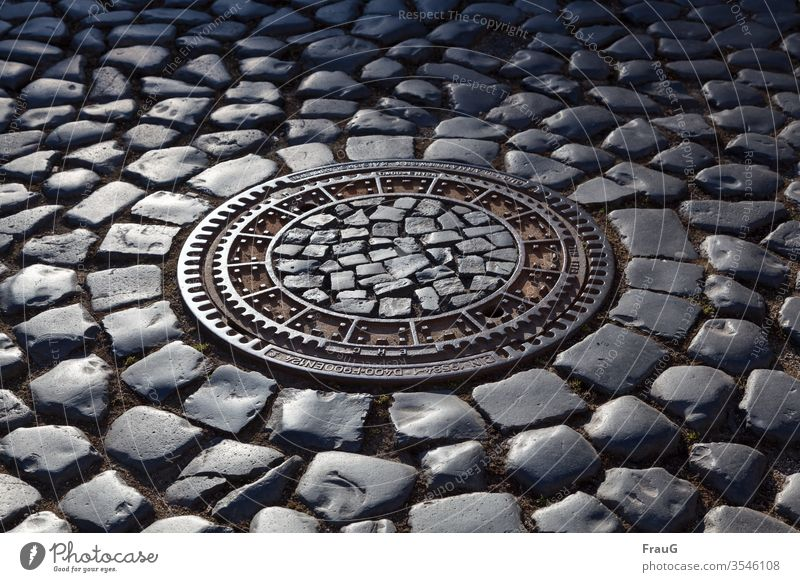 Manhole cover in the cobblestone pavement at evening light Old town Street Cobblestones Drainage system cobbled street Paving stone manhole cover Gully