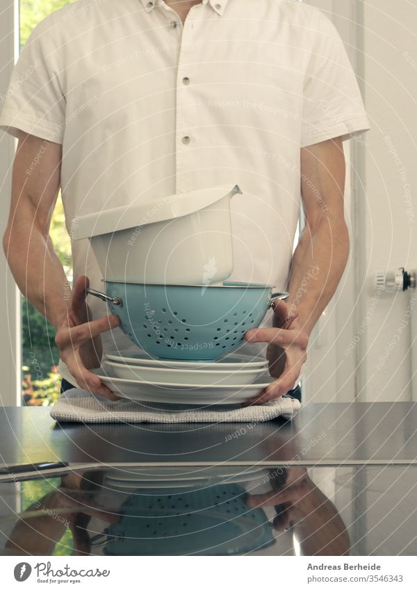 A middle-aged man in a kitchen holding washing dishes equipment service carrying husband smile sink european male activity house clean chores plate person