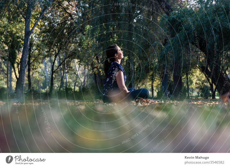 Beautiful woman seated on grass in front of sun doing yoga back balance concentration exercise fit fitness lotus meditate meditating meditation mental peace