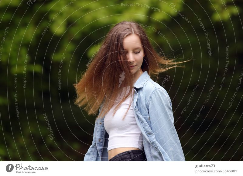 Portrait of a pretty cheerful young woman, teenager with long hair, in the park Half-profile Looking away portrait Motion blur Shadow Light Day Exterior shot