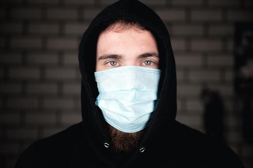 Portrait of young man wearing medical protective face mask for Covid-19 Coronavirus concept. Protect your health. background covid-19 business person fitness