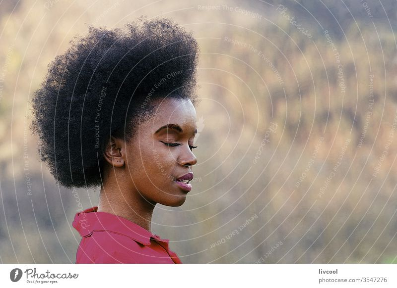 beautiful woman with afro hair meditating in nature black woman girl beauty pretty cool fashion style young people portrait lovely lifestyle garden closed eyes