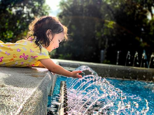 Girl Playing With Water Fountain in Sunshine lifestyle refreshment splashing sunlight toddler little person laughing heat sprinkler grass baby kids funny curly