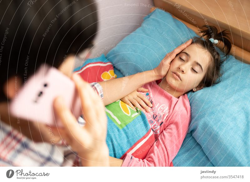 Mother worried about her daughter's temperature calling the doctor thermometer girl fever caucasian people care illness flu cold sick unwell sickness phone