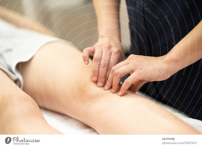 Physiotherapist woman doing a treatment on a woman's knee. physiotherapy leg chiropractor physical physiotherapist patient rehab clinic care health shoulder