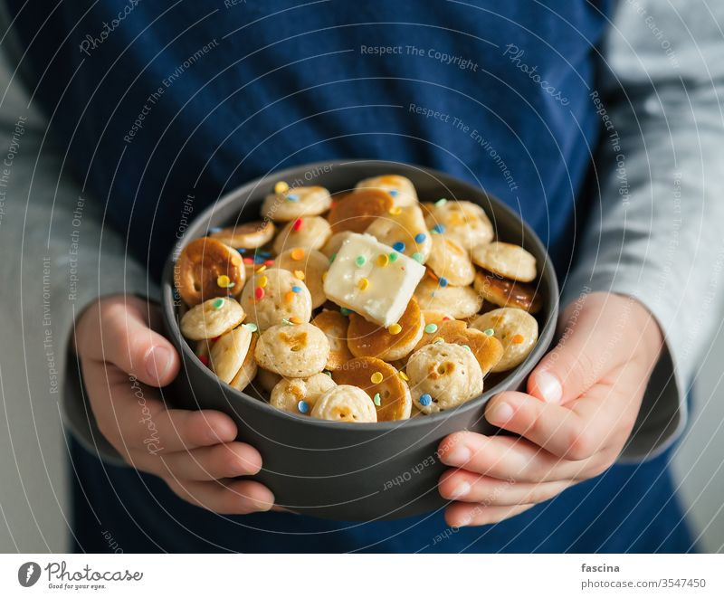 Pancake cereal in baby hands, copy space pancake cereal pancakes tiny pancakes mini pancakes child hold kid closeup sprinkles bowl food butter delicious recipe