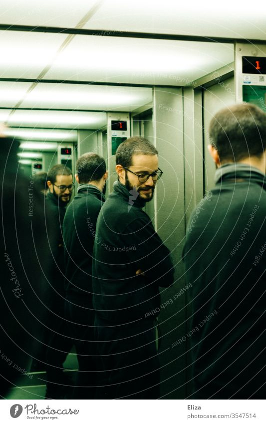 A man who is reflected several times in the mirrors of an elevator Man Eyeglasses Mirror reflection Personalities Multiple Personality infinitely Earnest