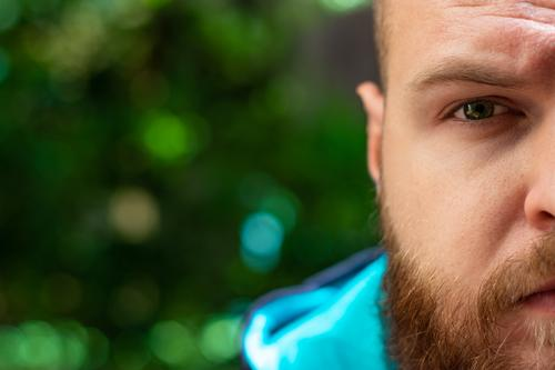 Half head of a bald bearded man visible, green serious sad eye shining in focus on green forest background. adult angry blue brutal casual caucasian confidence