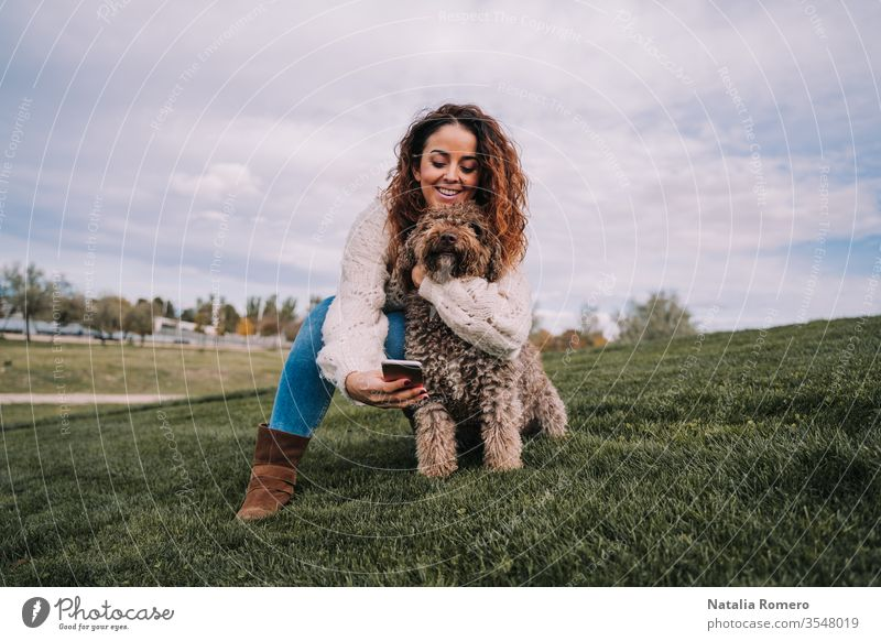 A beautiful woman is in the meadow with her dog. The owner is hugging her pet while trying to take a photo with her phone. The pet is a Spanish water dog with brown fur.