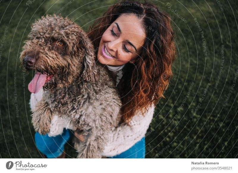 A beautiful woman is in the meadow with her dog. The owner is hugging her pet while looking at it with love. They are enjoying a day in the park. The pet is a Spanish water dog with brown fur.