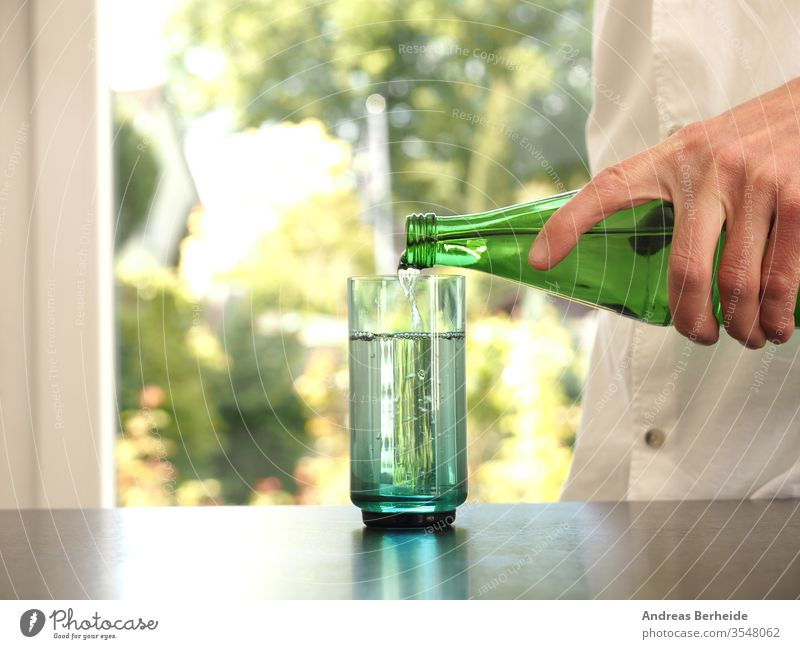 Mid aged man pouring water into a glass purity healthcare aqua fitness wellbeing mineral human blurred table person thirsty clear hold full garden bokeh wooden