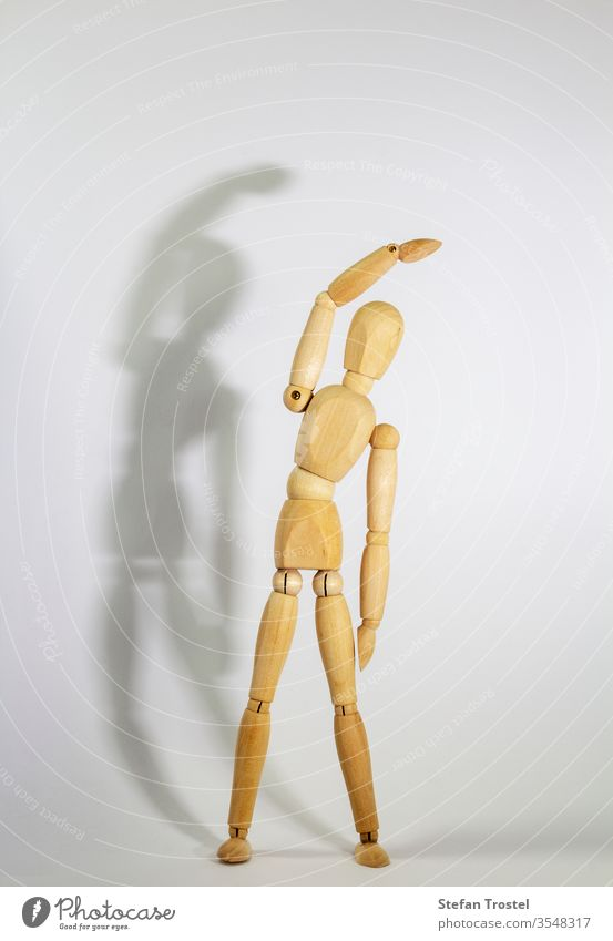 wooden doll during yoga practice Ansanas, triangle Trikonasana, in front of white background body dummy balance figurine fitness gesture sample model isolated