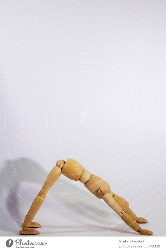 wooden doll during yoga practice Ansanas, looking down dog, in front of white background body dummy balance figurine fitness gesture sample model isolated
