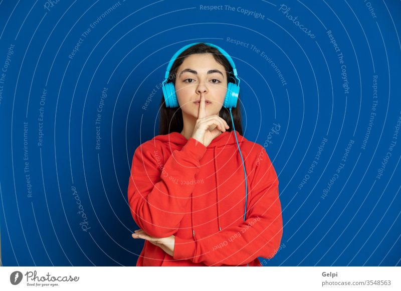Brunette young girl wearing red jersey person blue music enjoy dj headphones listen earphones technology modern relaxed silence believe portrait expression