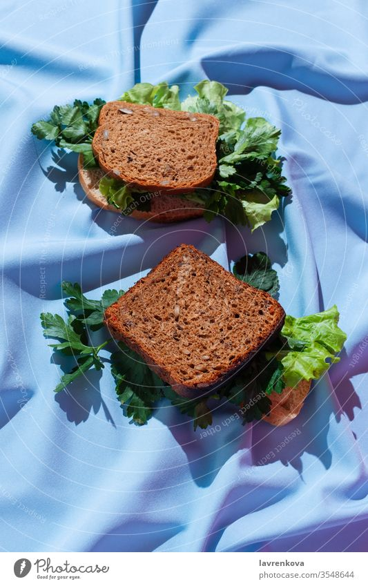 Pieces of rye bread with various greens on a drapery, concept of healthy sandwich, selective focus bright carbs delicious diet dish food fresh herbs ingredient