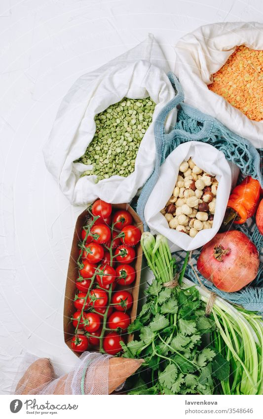Concept of zero waste sustainable food shopping: tomatoes, peas,various greens, hazelnuts etc in produce bags batata beans chilli coriander cotton bag diet eco