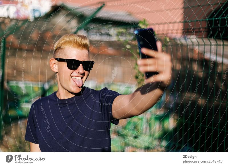 Young teenager with sunglasses taking a selfie outdoors male young phone 1 man person using portrait smartphone modern holding lifestyle people caucasian