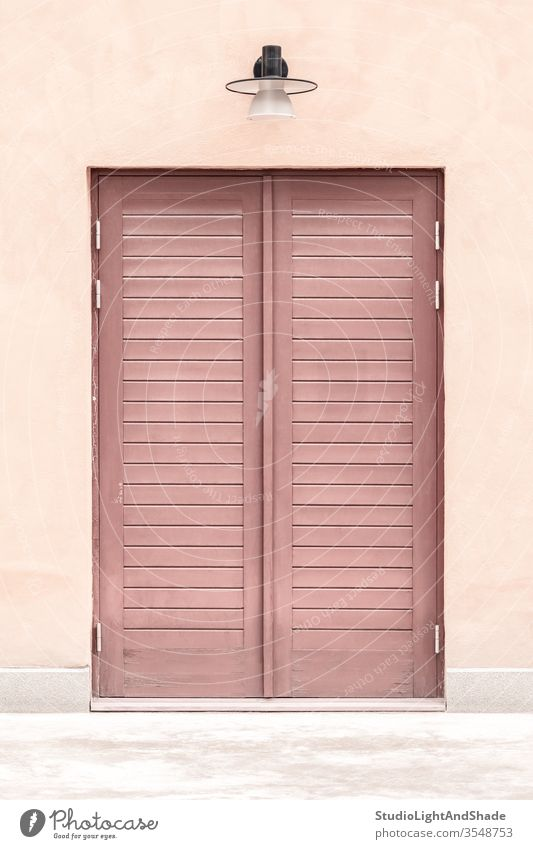 Pink building with a wooden door entrance pink red pastel closed house home lamp streetlamp streetlight exterior city town urban Europe European Stockholm
