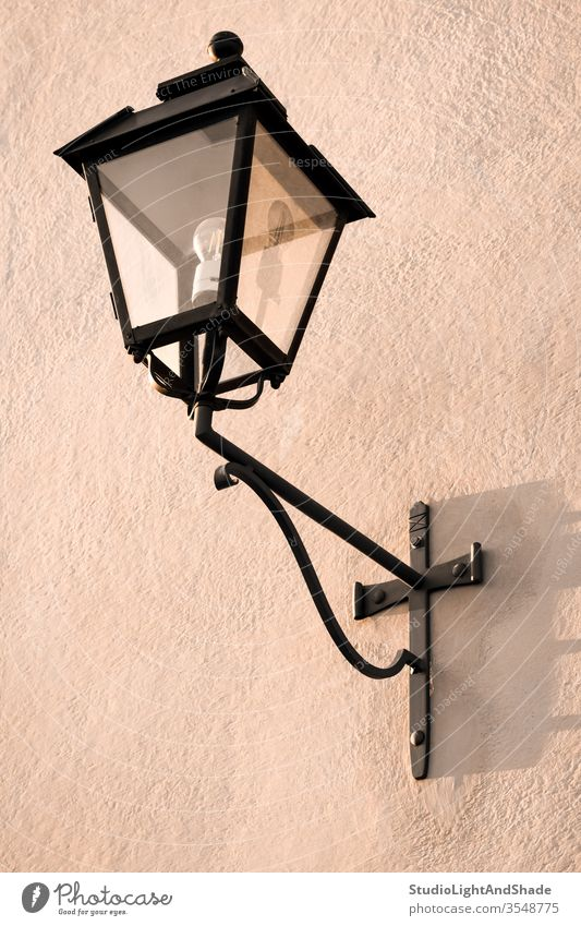 Vintage streetlight on a pink wall streetlamp lantern dusty pink pastel black electricity painted stone background texture surface metal vintage retro old