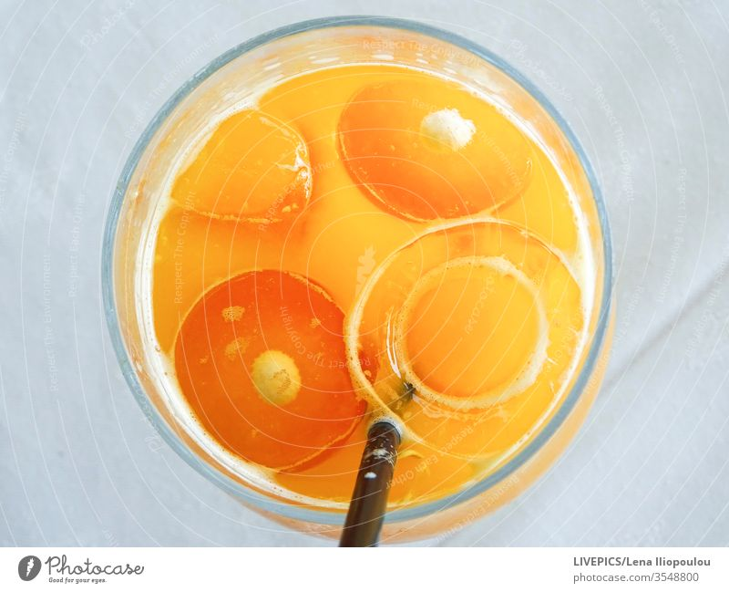 an orange juice in a glas, looks like a face Orange copy space eyes ice cubes light background mouth orange-slices nature freshness liquid drink refreshing