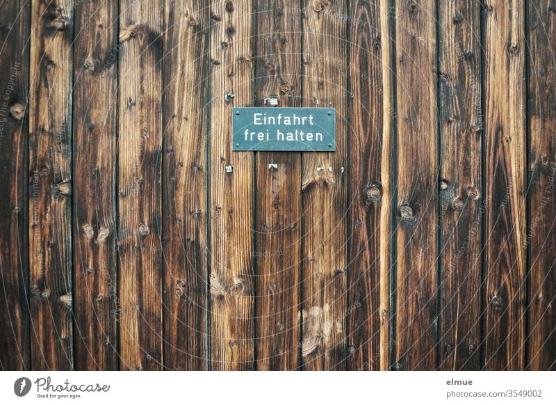 """Sign """"Keep driveway clear"""" on dark brown wooden boards Highway ramp (entrance) keep the driveway clear restriction Warning sign Expectation Destination"""