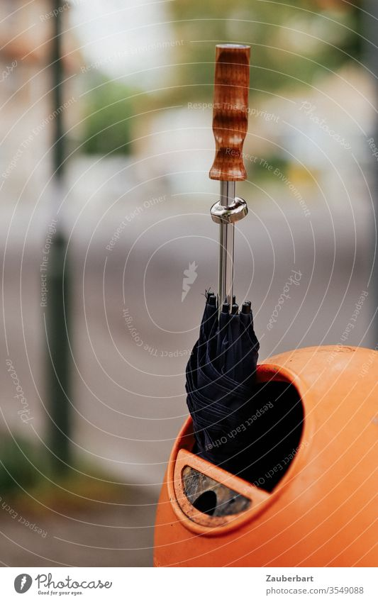 Black umbrella with wooden handle stuck in orange trash can Umbrella Door handle dustbin To plunge Rain Sun Shallow depth of field Oval Berlin BSR Street Trash