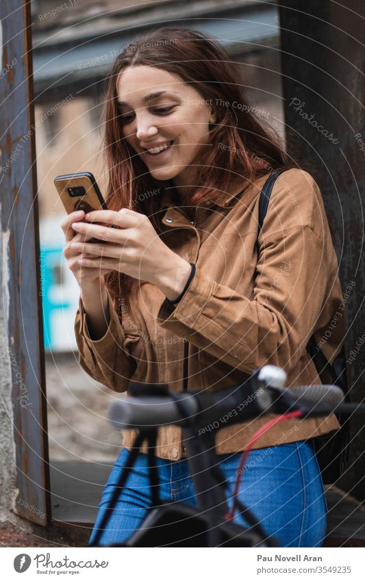 Young woman looking at smartphone on the street city life lifestyle urban beautiful communication connection device europe exterior gadget internet model wood