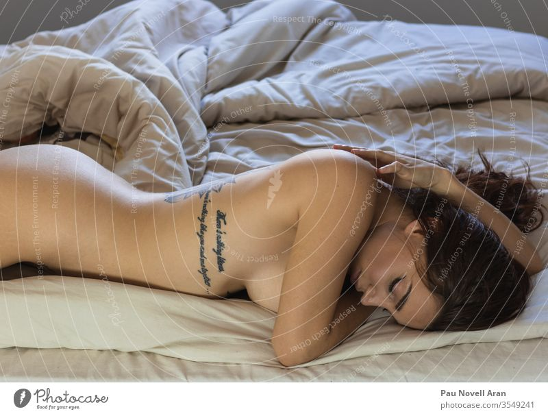 Sexy woman lying in bed sex cry naked alone girl sad sleep home indoors lazy orgasm sexy undressed apartment tattooed bedroom blanket white body ass dream