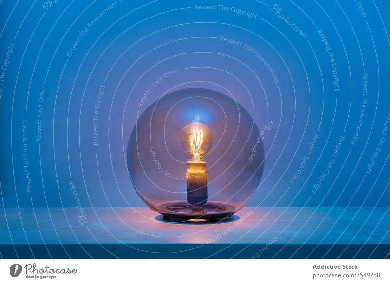 Turned on sphere lamp in dark room glass ball shelf light bulb electric blue design luminaire decoration modern turn on style minimal shape shadow creative dusk