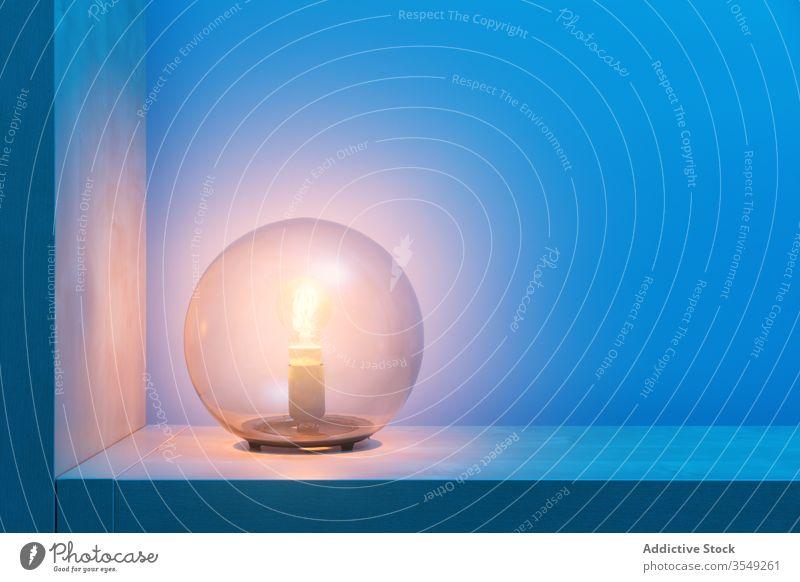 Lighting sphere lamp in corner in dark room illuminate glow electric night blue light light bulb glass ball shelf design bright decoration modern style minimal
