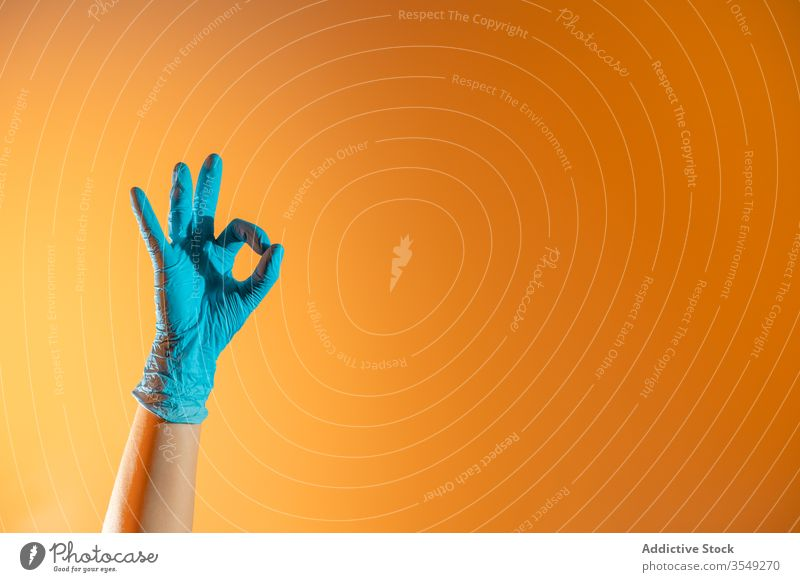Crop person in rubber glove showing ok sign gesture clean gesticulate concept horn symbol demonstrate protect hygiene healthy domestic housework household
