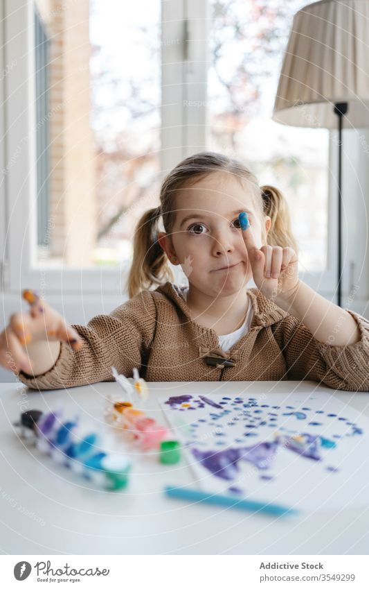Little girl showing finger with gouache while drawing in living room paint paper point playful cute preschool abstract picture creative kid child inspiration
