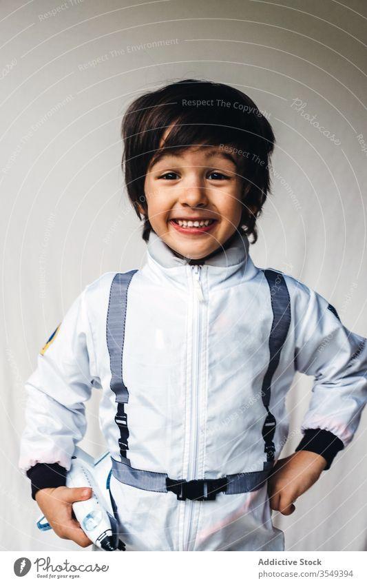 Adorable ethnic boy in cosmonaut costume on white background adorable spaceman toy spaceship positive child astronaut having fun kid spacesuit uniform smile