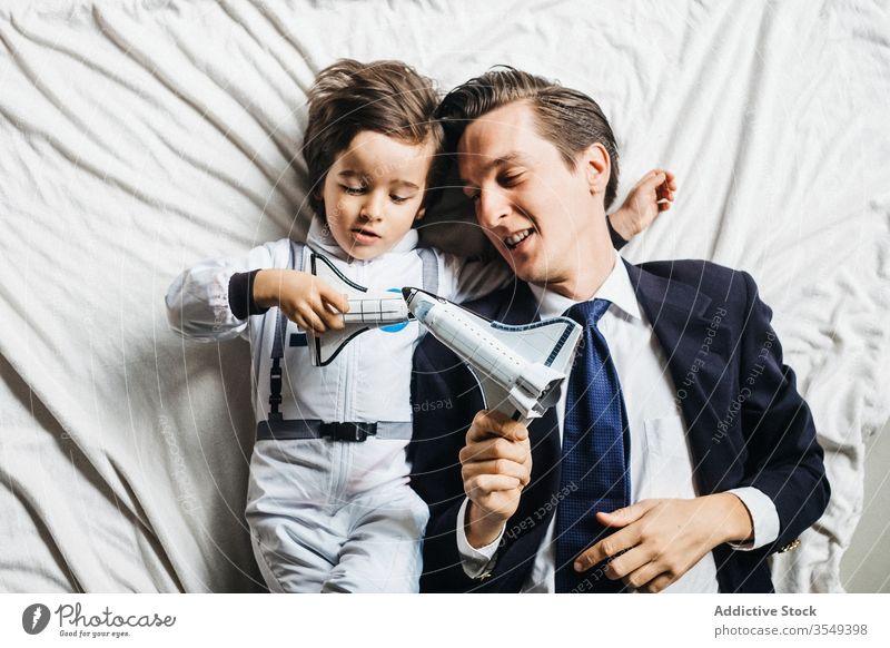 Content ethnic son and father lying on bed together astronaut costume boy dad play toy having fun diverse multiracial spacesuit parent spaceship smile kid