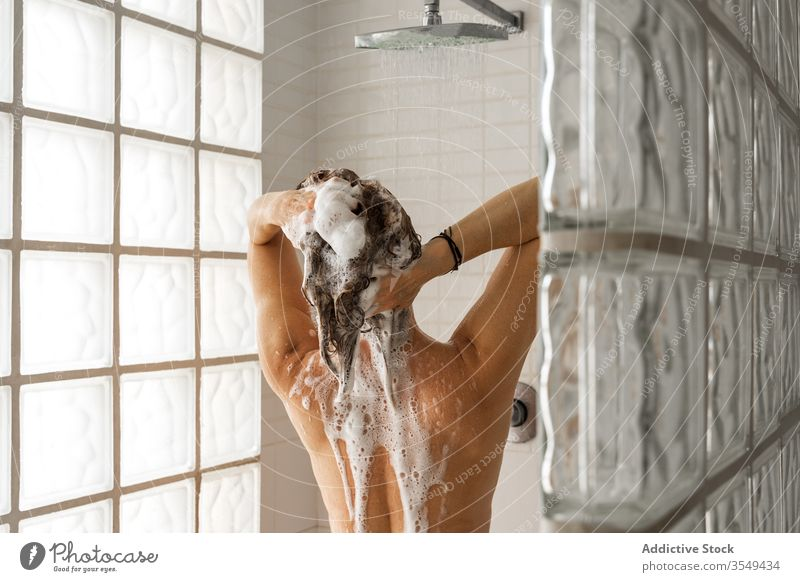 Woman washing hair and taking shower woman shampoo foam stall bathroom wet haircare female clean hygiene water stream treat relax fresh stand lady beauty