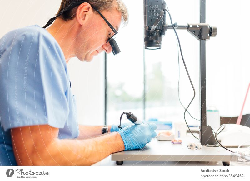 Dentist using microscope during work in classroom dentistry study education medicine equipment man tool laboratory professional doctor specialist health care