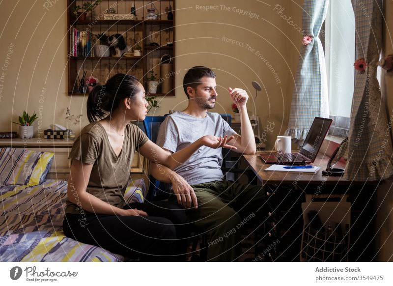 Multiethnic couple in love watching movie on laptop bedroom together discuss video using multiracial multiethnic diverse asian young casual outfit apparel wear