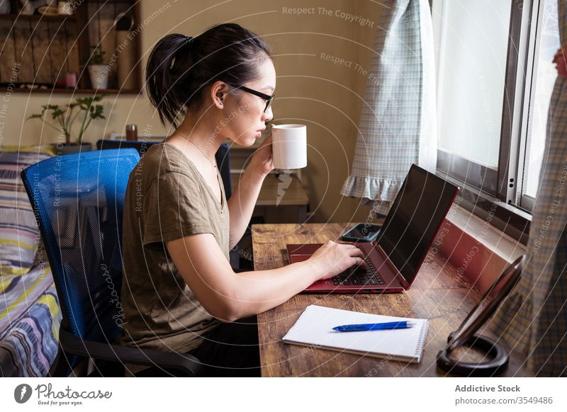 Busy female entrepreneur typing on laptop and drinking coffee woman home office busy using asian ethnic freelance concentrate self employed independent remote