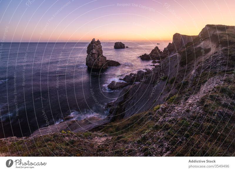 Amazing sunrise over rocky seashore coast rough sky ocean cliff calm scenery water colorful beautiful morning nature landscape scenic seascape tranquil travel