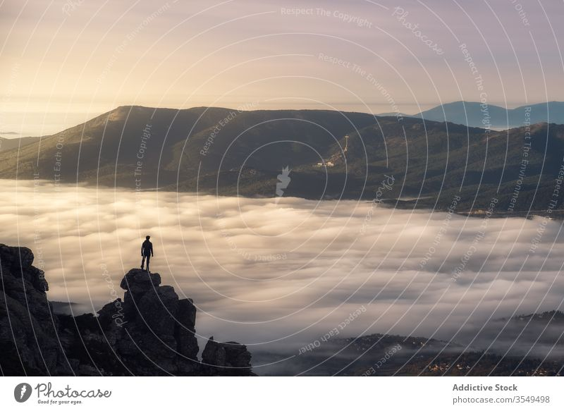 Traveler standing on top of rocky mountain cloud fog travel landscape nature hike cliff peak freedom inspiration valley tourist magnificent morning adventure