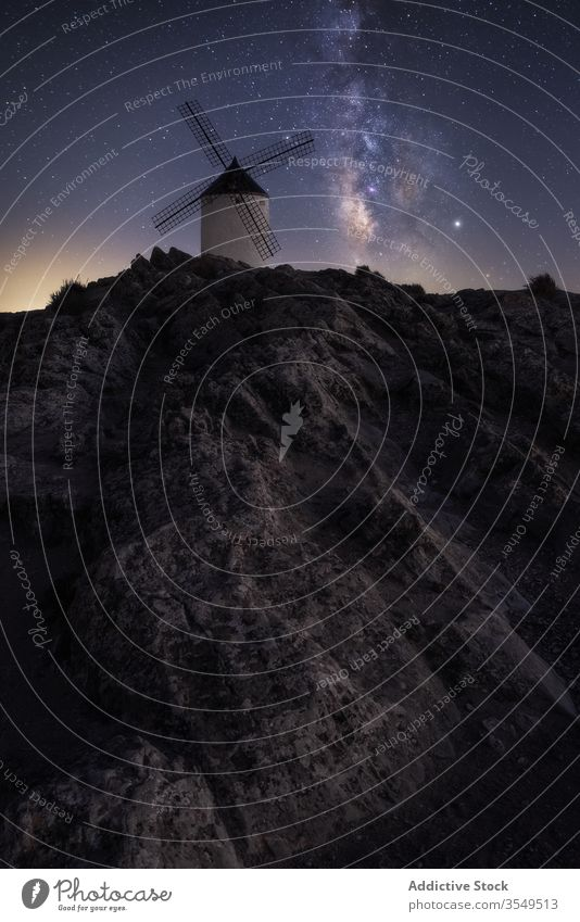 Rocky hill with dutch windmill at starry night landscape milky way mountain rock sky spectacular dark scenery magnificent evening amazing scenic galaxy universe