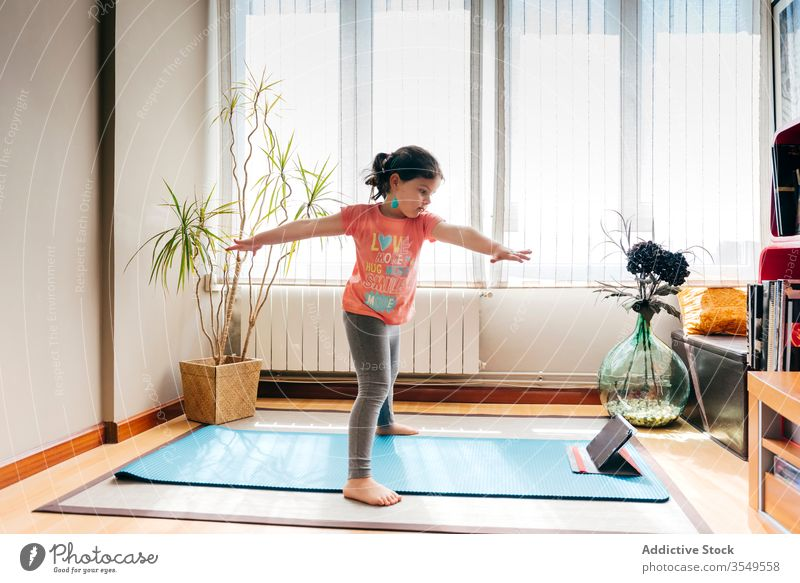 Joyful little girl doing yoga in light room kid pose mat video tablet tutorial balance practice at home stress relief watch harmony stretch flexible spirit