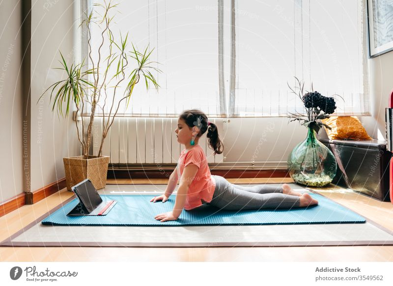 Little girl practicing yoga in cobra pose kid asana practice home tablet bhujangasana online flexible stretch little mat balance concentrate video tutorial