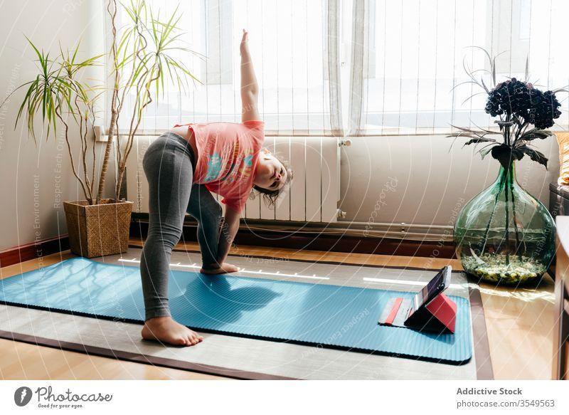 Little girl practicing yoga in extended side angle pose kid asana practice home tablet utthita parsvakonasana online flexible stretch little mat balance