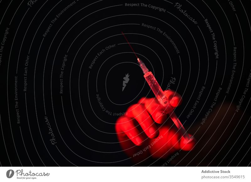Crop person holding syringe with medication in red light on black background vaccine cure injection hospital clinic covid 19 coronavirus infection disease