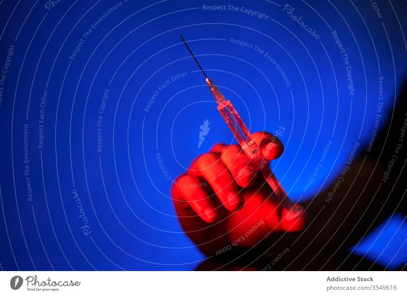 Crop person holding syringe with medication in red light on blue background vaccine cure injection hospital clinic covid 19 coronavirus infection disease