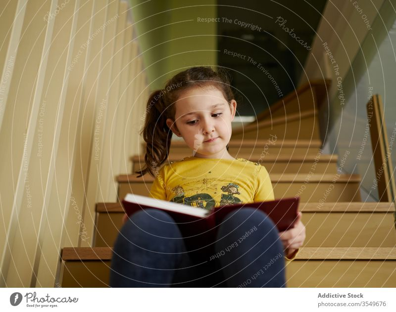 Curious small girl reading textbook on stairs in house kid schoolgirl child childhood bookworm alone interest literature learn develop imagination schoolkid